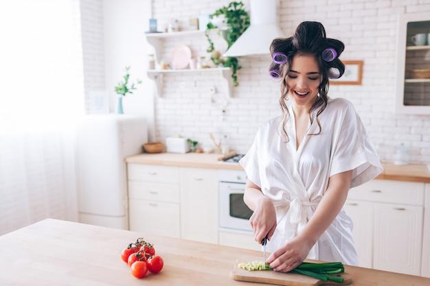 Jonge vrouwelijke huishoudstertribune bij bureau in keuken en besnoeiings groene ui. werk voorzichtig. snijd rode peper aan de linkerkant. alleen in de keuken. thuiswerken. sugar daddy betaalt alles.