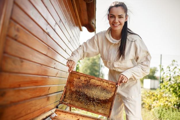 Jonge vrouwelijke imker haalt uit de korf een houten frame met honingraat.