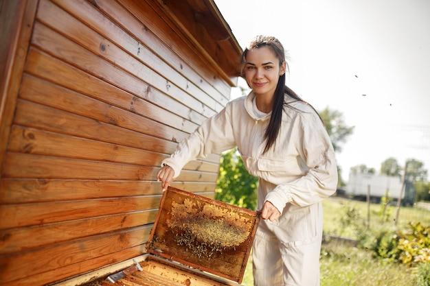 Jonge vrouwelijke imker trekt uit de korf een houten frame met honingraat. verzamel honing. bijenteelt concept.