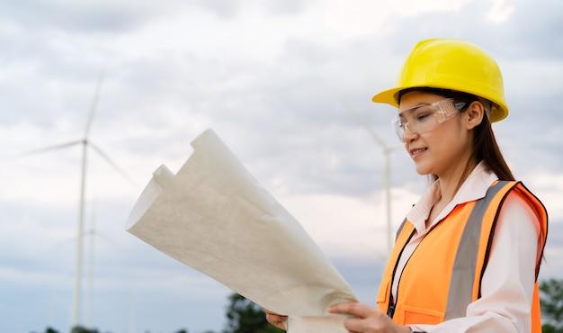 Jonge vrouwelijke ingenieur analyseert een blauwdruktekening van een windturbinepark