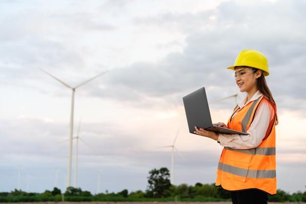 Jonge vrouwelijke ingenieur die met laptopcomputer werkt tegen windturbinepark