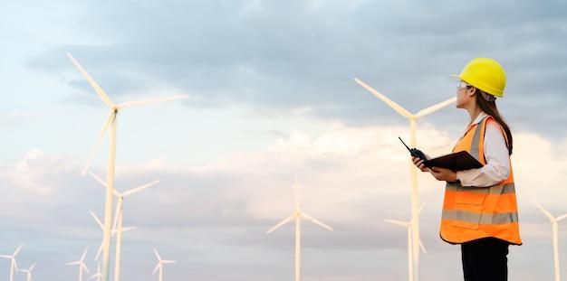 Jonge vrouwelijke ingenieur die walkie-talkie gebruikt en klembord leest om het systeem tegen windturbinepark te controleren
