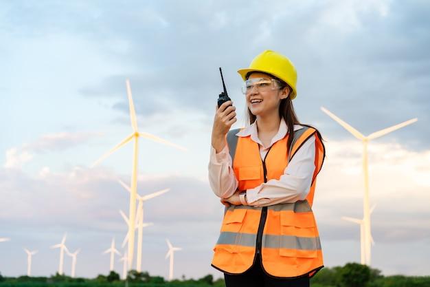 Jonge vrouwelijke ingenieur die walkie-talkie gebruikt om systeem tegen windturbinepark te controleren