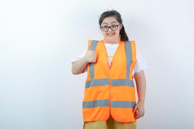 Jonge vrouwelijke ingenieur in glazen duimen opgevend op witte muur