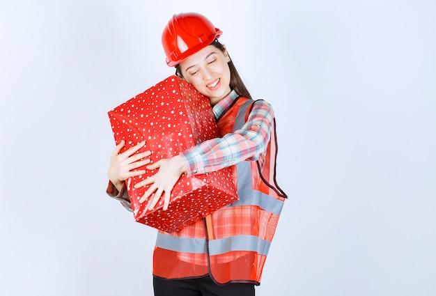 Jonge vrouwelijke ingenieur in rode helm knuffelt geschenkdoos.