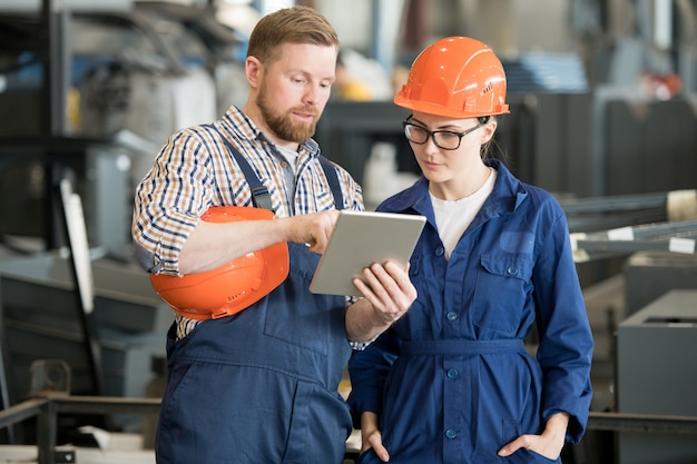 Jonge vrouwelijke ingenieur in uniform en helm kijken naar tablet-display terwijl u luistert naar collega-uitleg van gegevens