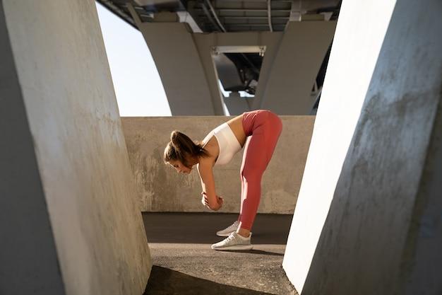 Jonge vrouwelijke jogger bereidt zich voor op het uitvoeren van werk, benen strekkend buiten onder een brug