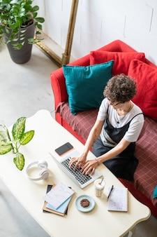 Jonge vrouwelijke kantoor aan huis manager op afstand werken voor laptop zittend door bureau in de thuisomgeving
