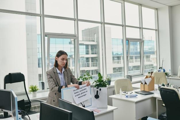 Jonge vrouwelijke kantoormedewerker of secretaresse die papier aanbrengt met notitie over haar thuiswerken en beschikbaar zijn op telefoon, e-mail of messenger