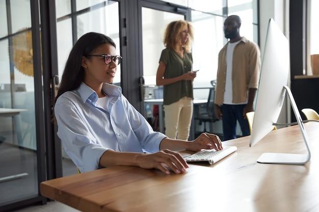 Jonge vrouwelijke kantoormedewerker van gemengd ras die op de computer werkt terwijl ze op haar werkplek zit