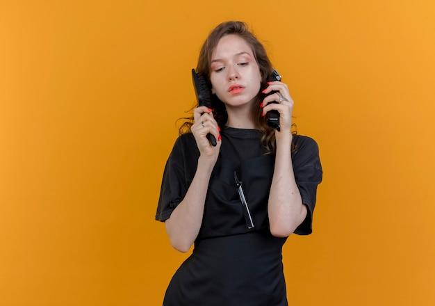 Jonge vrouwelijke kapper dragen uniforme bedrijf tondeuse en kam in de buurt van hoofd naar beneden te kijken