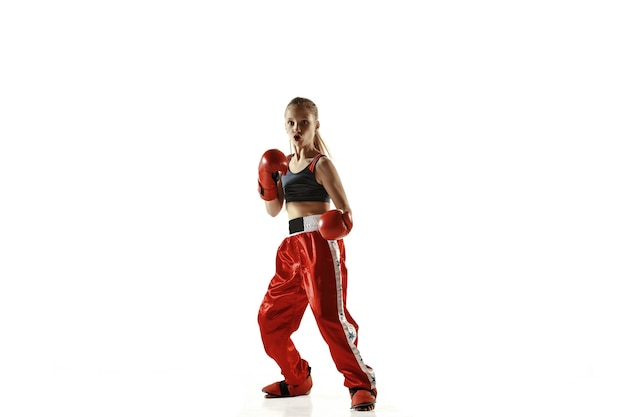 Jonge vrouwelijke kickboks vechter opleiding geïsoleerd op een witte muur. kaukasisch blond meisje in rode sportkleding beoefenen in vechtsporten. concept van sport, gezonde levensstijl, beweging, actie, jeugd.