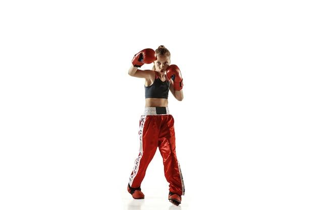 Jonge vrouwelijke kickboksen vechter opleiding geïsoleerd op een witte muur. kaukasisch blond meisje in rode sportkleding beoefenen in vechtsporten. concept van sport, gezonde levensstijl, beweging, actie, jeugd.