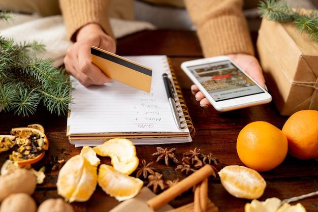 Jonge vrouwelijke klant creditcard en smartphone boven tafel te houden tijdens het bestellen van kerstcadeaus voor familie