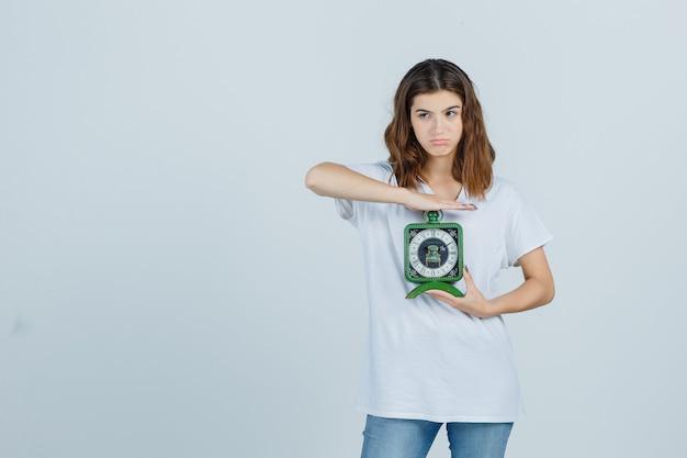 Jonge vrouwelijke klok in wit t-shirt, spijkerbroek en op zoek aarzelend, vooraanzicht.