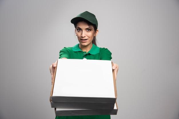 Jonge vrouwelijke koerier die pizzadozen weggeeft