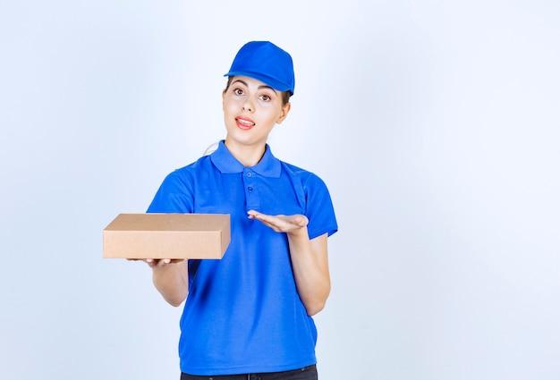 Jonge vrouwelijke koerier in blauw uniform met kartonnen doos met open ruimte.