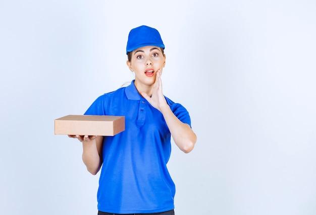 Jonge vrouwelijke koerier in blauwe dop die een kartonnen doos vasthoudt en iemand belt.