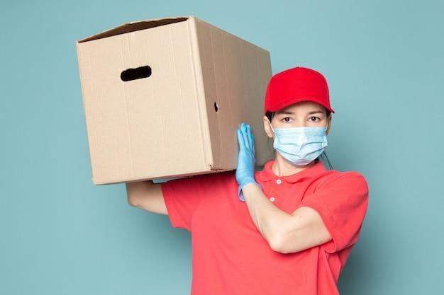 Jonge vrouwelijke koerier in roze t-shirt rode dop blauw steriel masker met doos op de blauwe muur