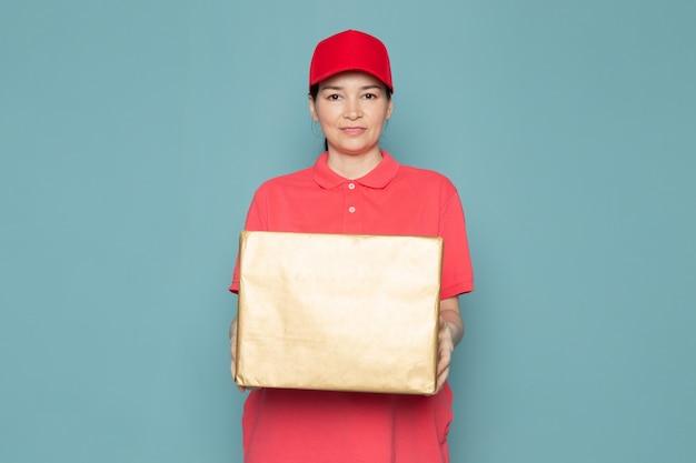Jonge vrouwelijke koerier in roze t-shirt rode dop doos houden op de blauwe muur