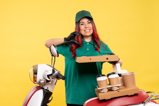 Jonge vrouwelijke koerier met bezorgkoffie en eten op geel