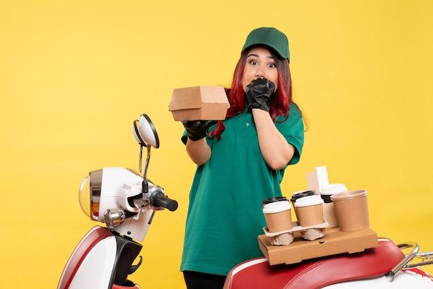 Jonge vrouwelijke koerier met bezorgkoffie en voedselpakket op geel