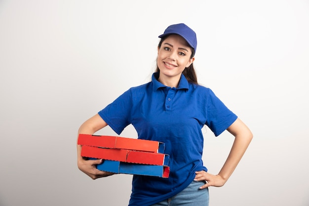 Jonge vrouwelijke koerier met karton van pizza en klembord