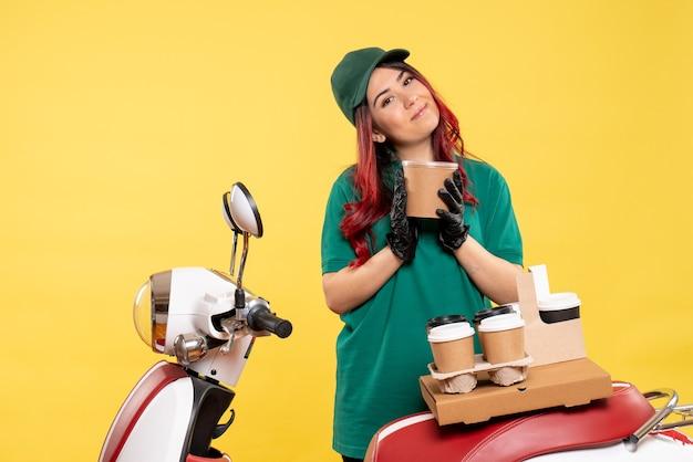Jonge vrouwelijke koerier met koffie en dessert op geel