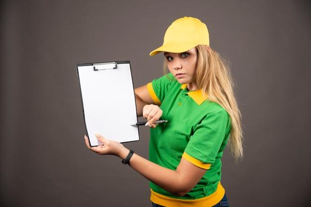 Jonge vrouwelijke koerier met potlood die klembord toont.