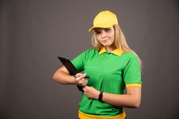 Jonge vrouwelijke koerier met potlood en klembord.