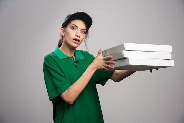 Jonge vrouwelijke koerier poseren met pizzadozen