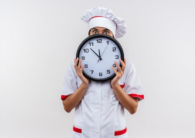 Jonge vrouwelijke kok die chef-kok uniform bedekt gezicht met muurklok draagt op geïsoleerde witte muur met exemplaarruimte