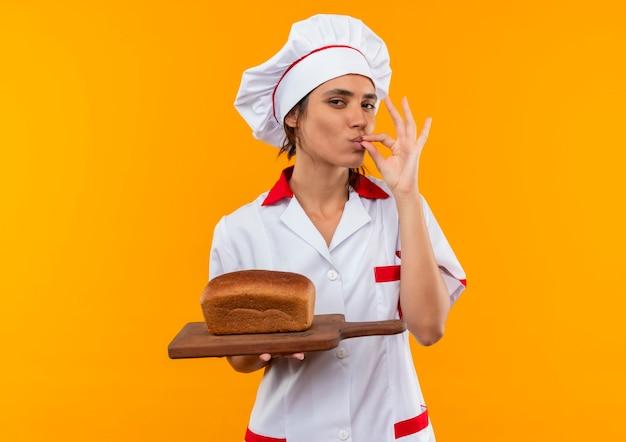 Jonge vrouwelijke kok die chef-kok uniform draagt dat brood op snijplank houdt en heerlijk gebaar toont op geïsoleerde gele muur met exemplaarruimte