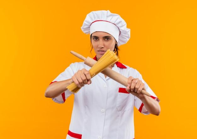 Jonge vrouwelijke kok die chef-kok uniform draagt en spaghetti met deegroller kruist op geïsoleerde gele muur met exemplaarruimte