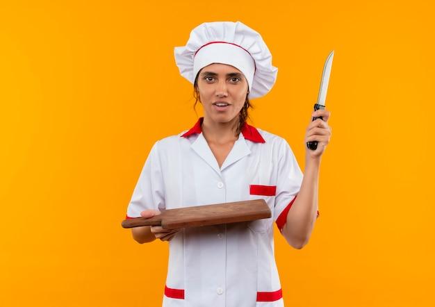 Jonge vrouwelijke kok die chef-kok uniforme snijplank en mes op geïsoleerde gele muur met exemplaarruimte houdt