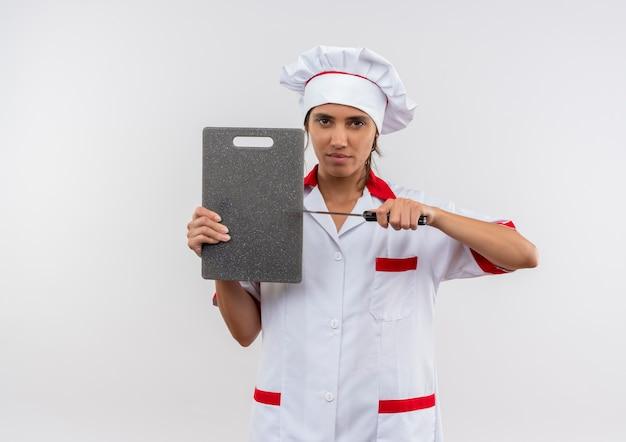 Jonge vrouwelijke kok die chef-kok uniforme snijplank en mes op geïsoleerde witte muur met exemplaarruimte houdt