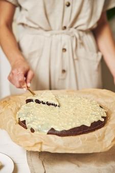 Jonge vrouwelijke kok die een heerlijke chocoladetaart maakt met room op een witte tafel