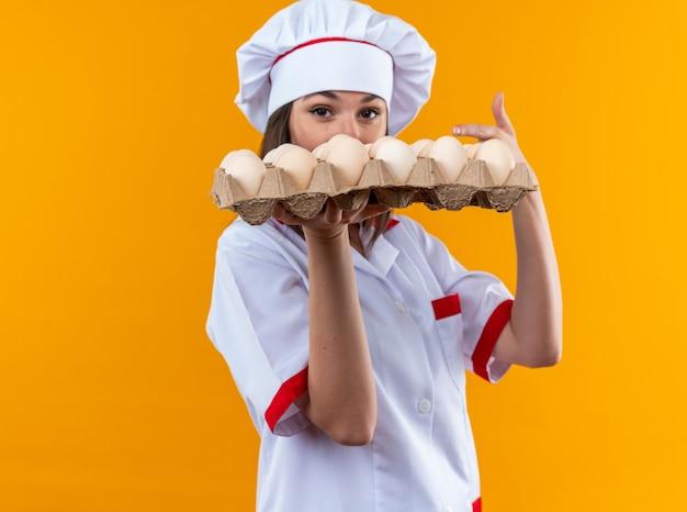 Jonge vrouwelijke kok die een uniform van de chef-kok draagt en wijst naar een partij eieren geïsoleerd op een oranje muur