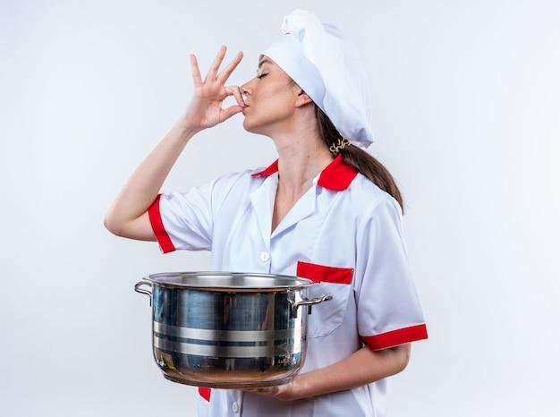 Jonge vrouwelijke kok die een uniforme chef-kok draagt die een steelpan houdt die op witte muur wordt geïsoleerd