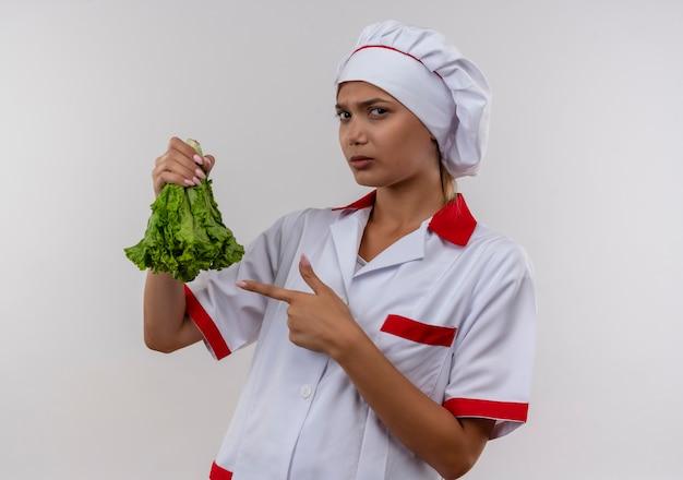 Jonge vrouwelijke kok dragen chef-kok uniform wijst vinger naar salade in haar hand op geïsoleerde witte muur