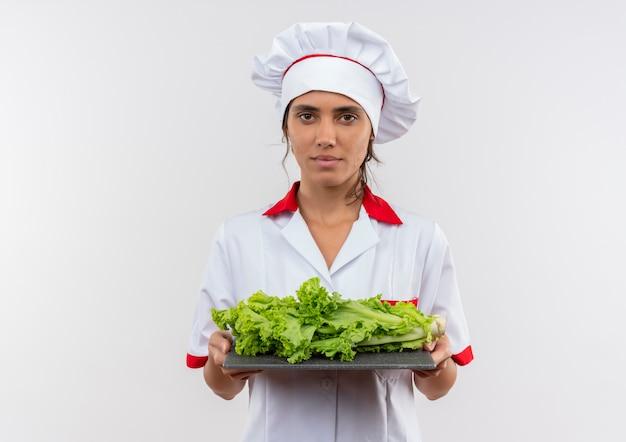 Jonge vrouwelijke kok dragen chef-kok uniforme bedrijf salade op snijplank op geïsoleerde witte muur met kopie ruimte