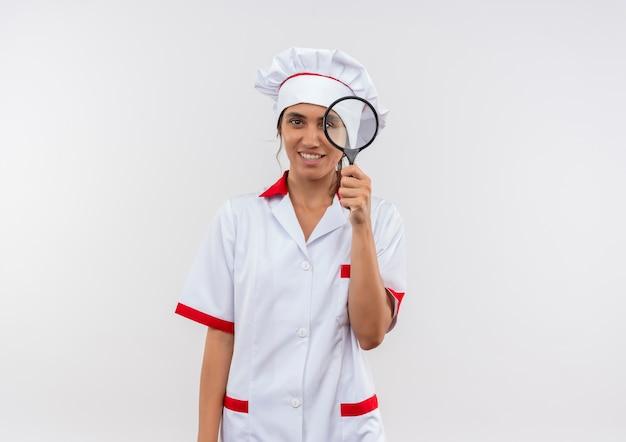 Jonge vrouwelijke kok dragen chef-kok uniforme bedrijf vergrootglas op geïsoleerde witte muur met kopie ruimte