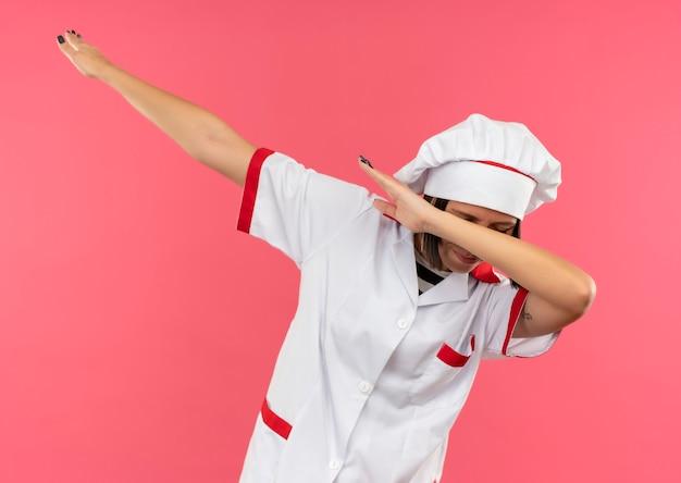 Jonge vrouwelijke kok in chef-kok uniform doet schar gebaar met gesloten ogen geïsoleerd op roze achtergrond