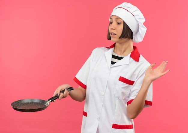 Jonge vrouwelijke kok in chef-kok uniform houden en koekenpan kijken en hand opheffen geïsoleerd op roze achtergrond
