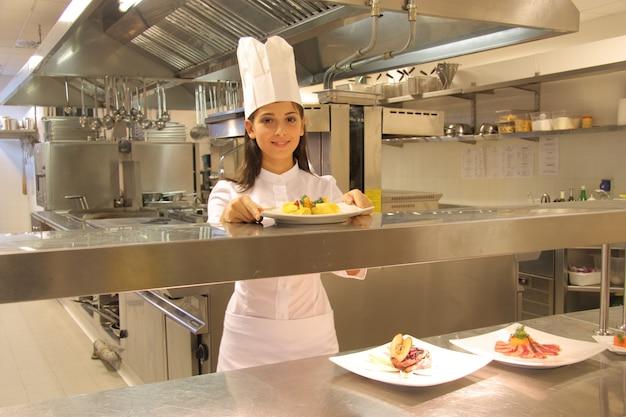 Jonge vrouwelijke kok in een keuken van een restaurant