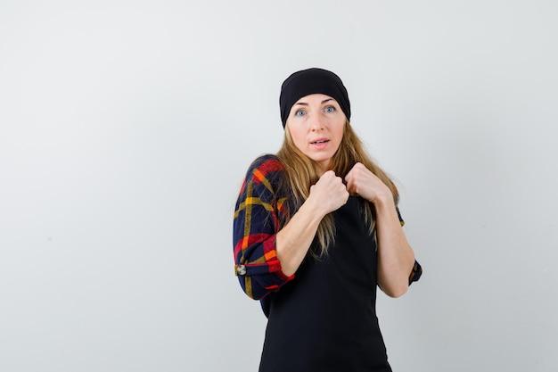 Jonge vrouwelijke kok in een zwarte schort bereid om te vechten