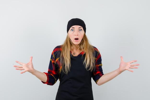 Jonge vrouwelijke kok in een zwarte schort wordt verrast