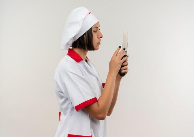 Jonge vrouwelijke kok in eenvormige chef-kok die zich in profielmening bevindt en mes bekijkt dat op witte achtergrond met exemplaarruimte wordt geïsoleerd