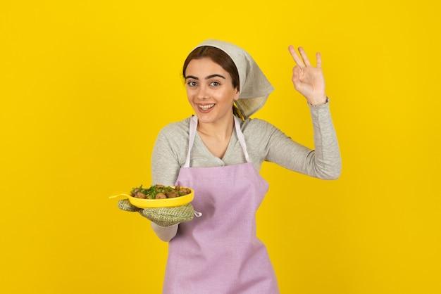 Jonge vrouwelijke kok in schort met bord gebakken champignons en ok teken tonen.