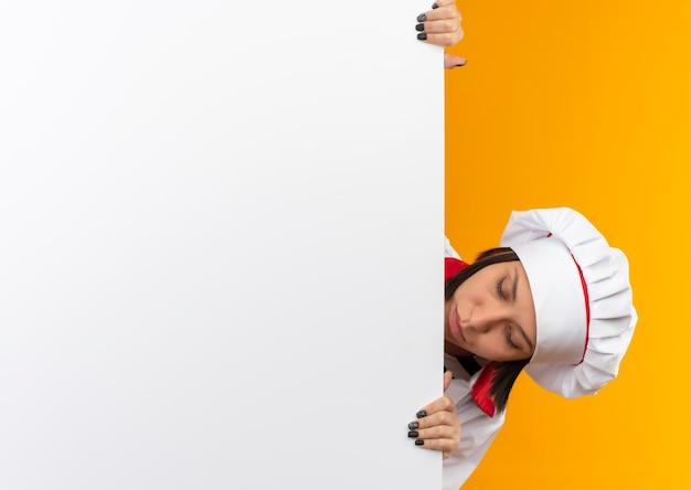 Jonge vrouwelijke kok in uniform chef-kok jonge vrouwelijke kok in uniform chef-kok houden en kijken van achter witte muur naar muur geïsoleerd op achtergrond met kopie ruimte